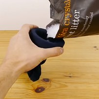 5. Fill up the sock with the cat litter, then tie a knot in the end.